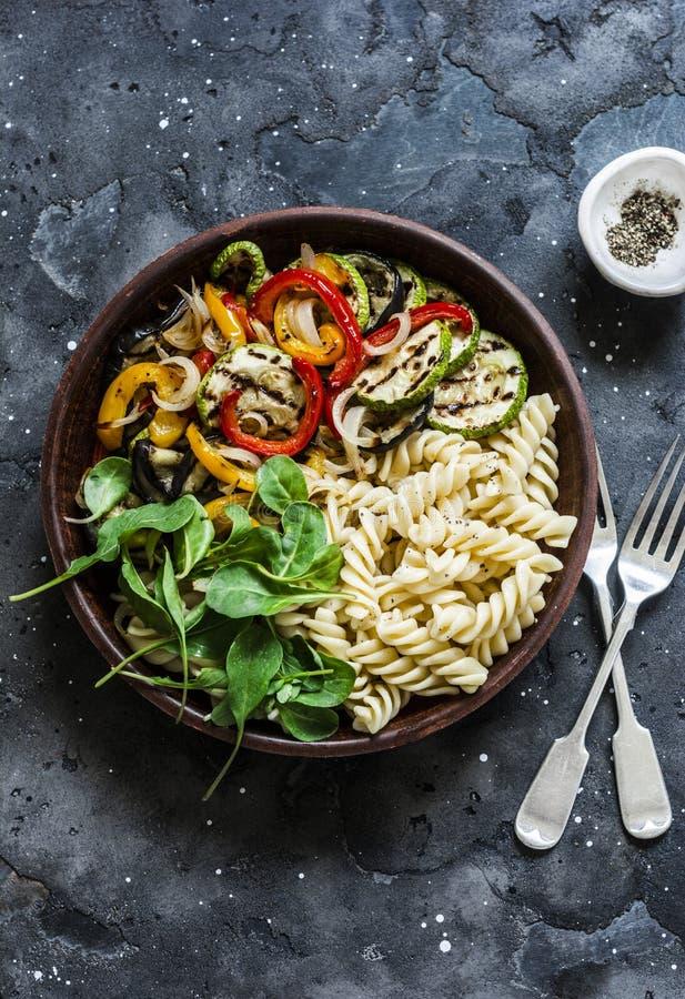 Зажаренный салат овощей и antipasti макаронных изделий fusilli на темной предпосылке, взгляде сверху стоковая фотография