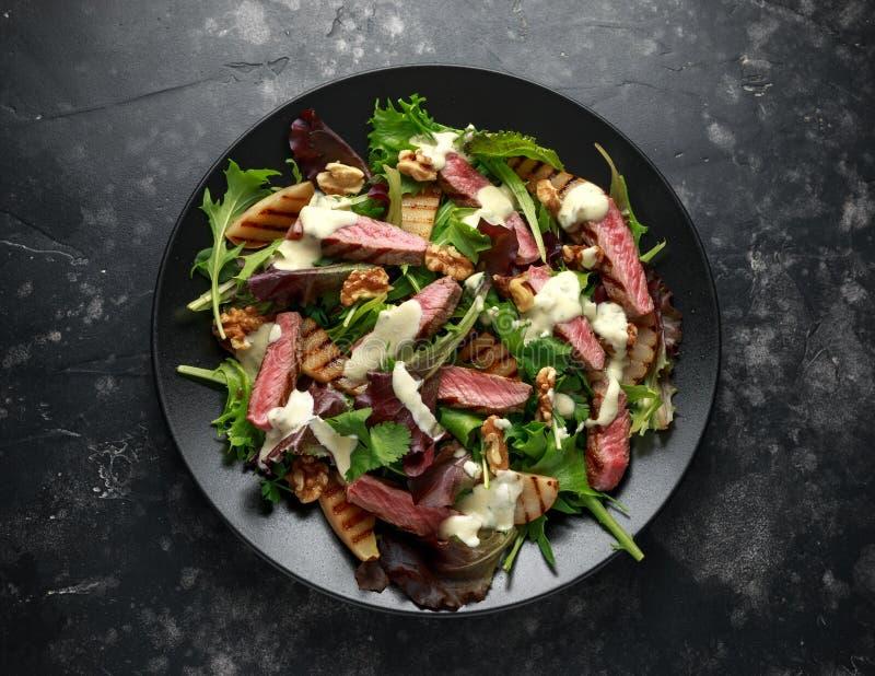 Зажаренный салат стейка говядины с грушами, грецкими орехами и овощами зеленых цветов и соусом голубого сыра E стоковые изображения