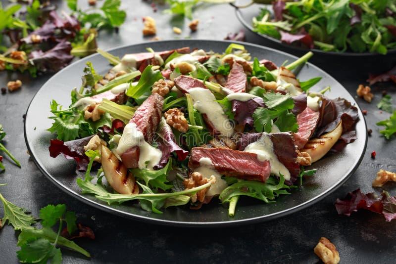 Зажаренный салат стейка говядины с грушами, грецкими орехами и овощами зеленых цветов и соусом голубого сыра E стоковая фотография