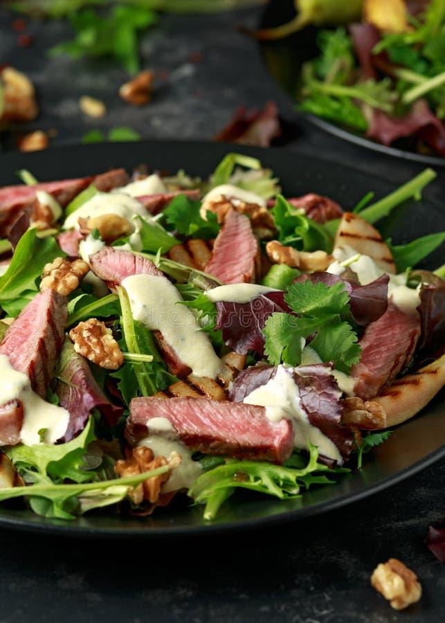 Зажаренный салат стейка говядины с грушами, грецкими орехами и овощами зеленых цветов и соусом голубого сыра E стоковые изображения rf