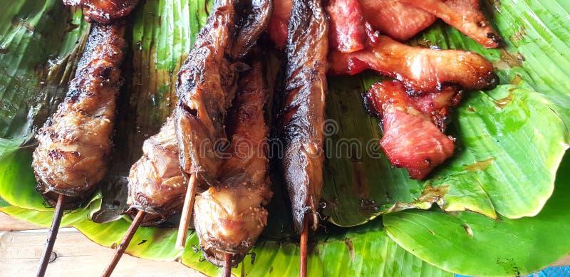Зажаренный сом или зажаренная в духовке свинина и куриная грудка на лист банана для продажи в тайском местном ресторане еды стоковая фотография