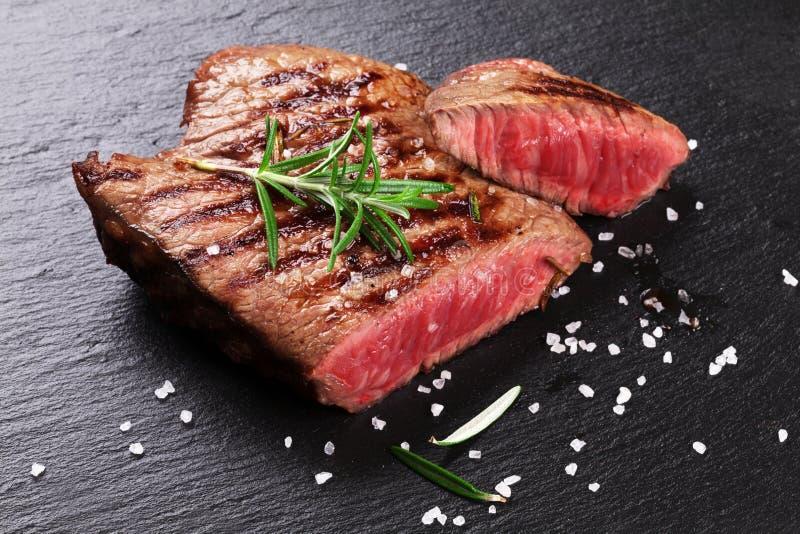 Зажаренный стейк говядины с розмариновым маслом, солью и перцем стоковые фото