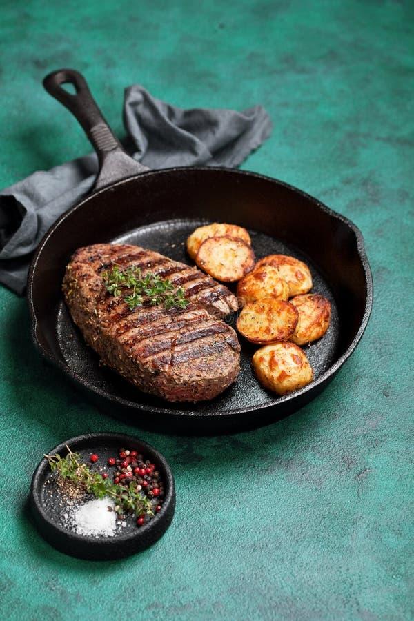 Зажаренный стейк говядины и испеченная картошка в skillet литого железа стоковые фотографии rf