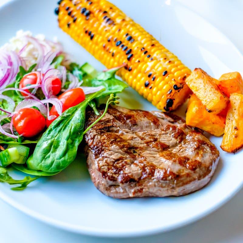 Зажаренный стейк говядины с некоторым салатом стоковое фото rf
