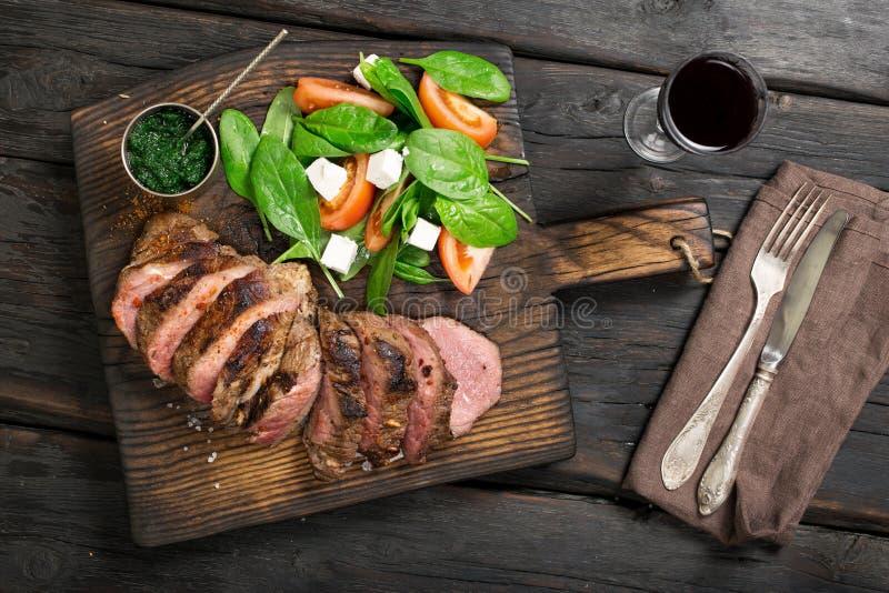 Зажаренный стейк говядины с салатом, соусом chimichurri и красным вином стоковые изображения