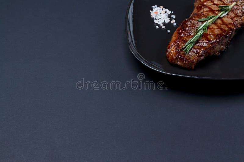 Зажаренный стейк Нью-Йорка с розмариновым маслом и розовым himalanian солью o стоковое изображение rf