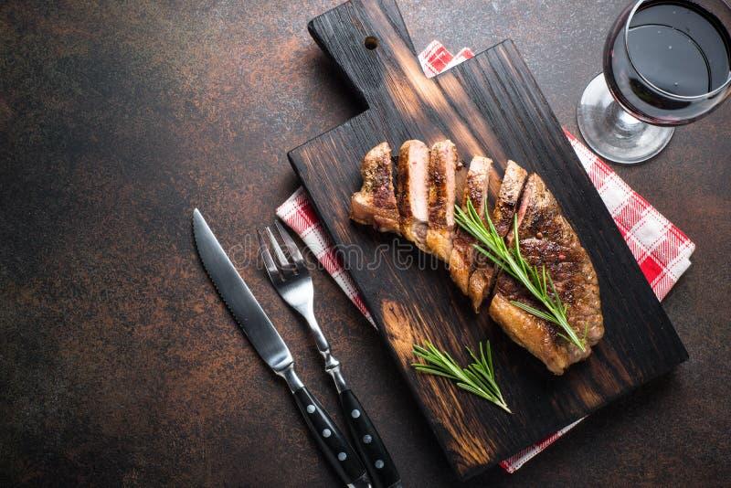 Зажаренный стейк striploin говядины с красным бокалом стоковое фото