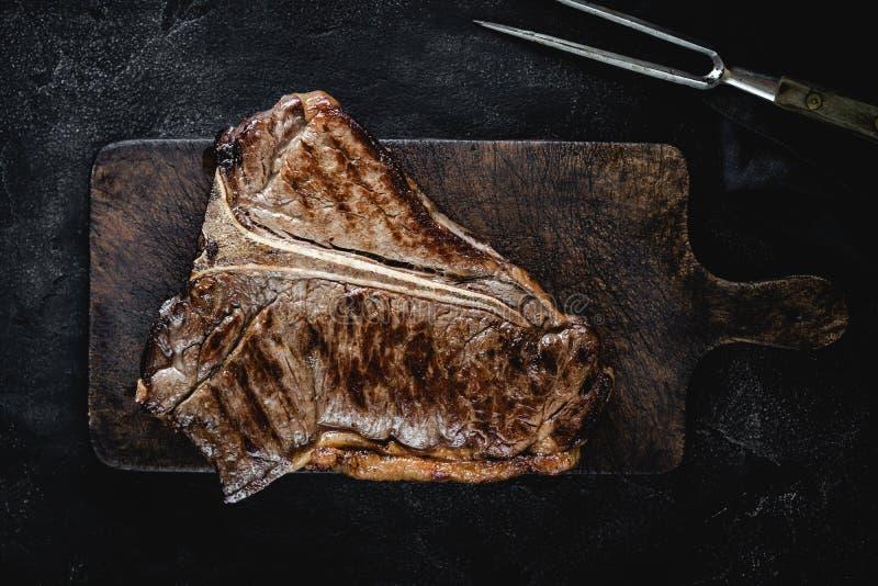 Зажаренный сухой достигший возраста стейк T-косточки на винтажной разделочной доске стоковое изображение rf