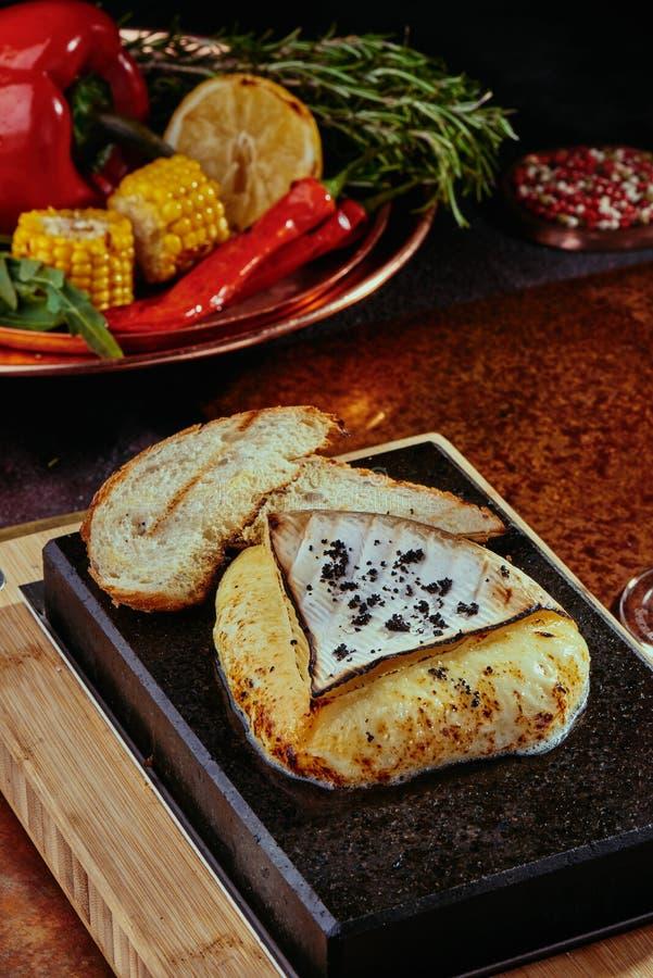 Зажаренный сыр камамбера на черной квадратной каменной плите с тостом медная предпосылка стоковые изображения rf