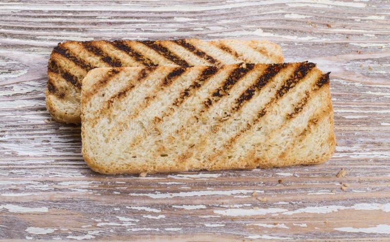 2 зажаренный тост на деревянной предпосылке стоковые изображения rf