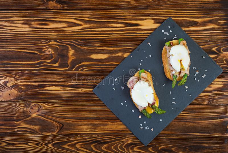 Зажаренный тост со спаржей в беконе и краденном яйце на деревянной предпосылке стоковая фотография rf