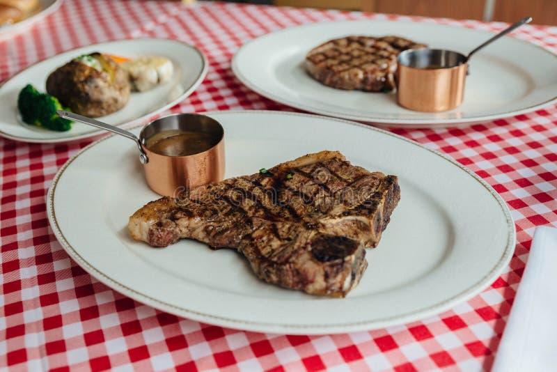Зажаренный углем стейк T-косточки wagyu служил с соусом BBQ и пек картошку в белой плите на красной и белой скатерти картины стоковая фотография rf