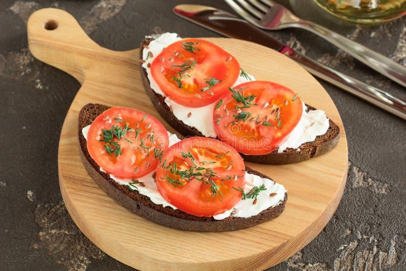 Зажаренный хлеб с сыром, томатами и зелеными цветами для обеда стоковое фото rf