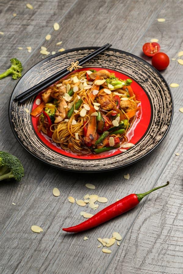 Зажаренный цыпленок на черной плите, расположенной рядом с овощами, красными перцами и палочками стоковая фотография rf