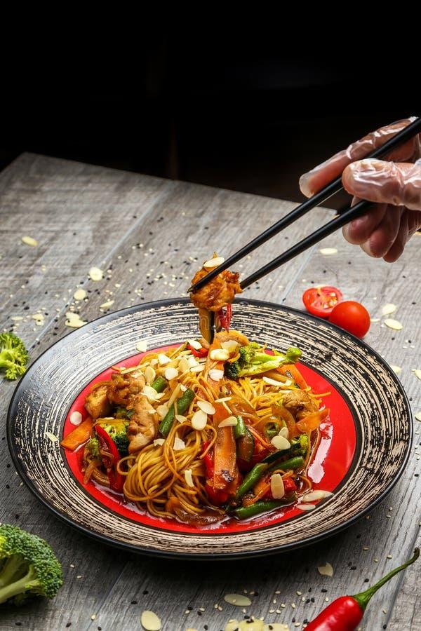 Зажаренный цыпленок на черной плите, расположенной рядом с овощами, красными перцами и палочками стоковые фотографии rf