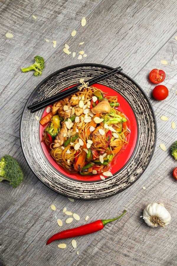 Зажаренный цыпленок на черной плите, расположенной рядом с овощами, красными перцами и палочками стоковая фотография