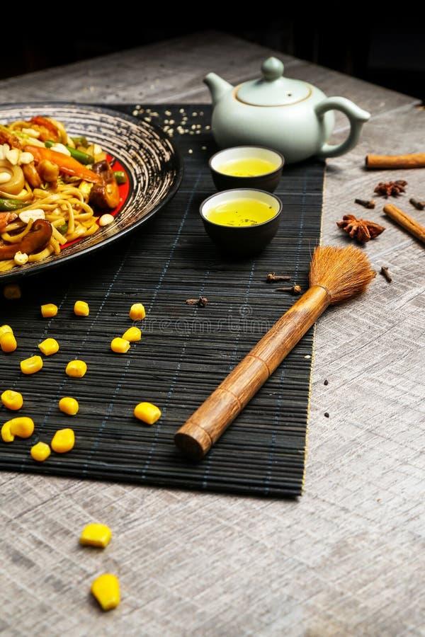 Зажаренный цыпленок на черной плите, расположенной рядом с овощами, красными перцами и палочками стоковые изображения