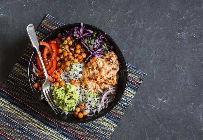 Зажаренный цыпленок, рис, пряные нуты, месиво авокадоа, капуста, шар Будды перца на темной предпосылке, взгляд сверху Сбалансиров стоковые фотографии rf