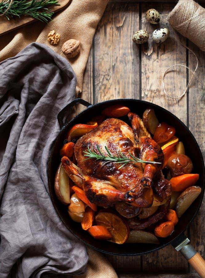 Зажаренный цыпленок с картошками и овощами в сковороде чугуна на деревянной деревенской предпосылке Конец-вверх Взгляд стоковое фото rf