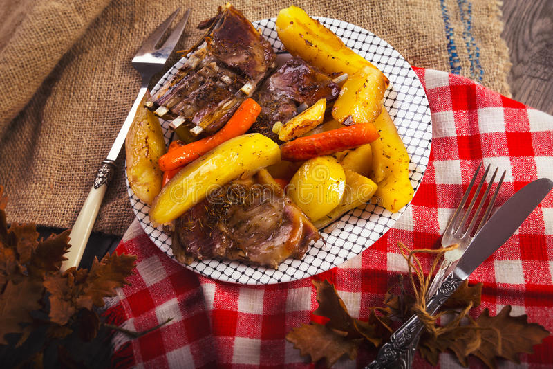 Зажаренный шкаф отбивных котлет овечки с картошками овощи стоковая фотография