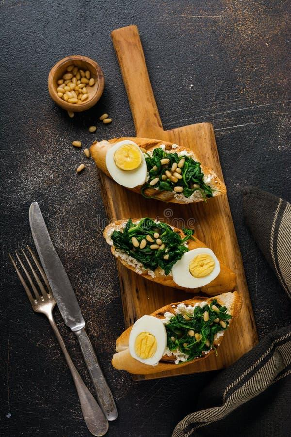 Зажаренный шпинат, яйцо и сэндвичи или bruschetta сосны чокнутые на светлой предпосылке Очень вкусный здоровый завтрак или закуск стоковые фотографии rf