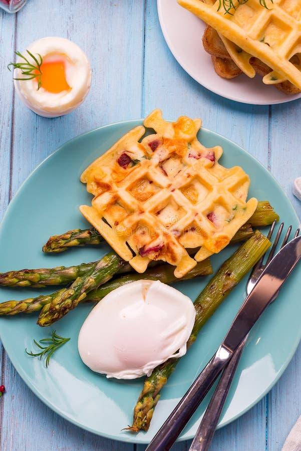 Зажаренный waffle с зеленым цветом закипел спаржу с краденным яичком, с солью и специями на голубой плите как здоровый завтрак стоковое изображение rf