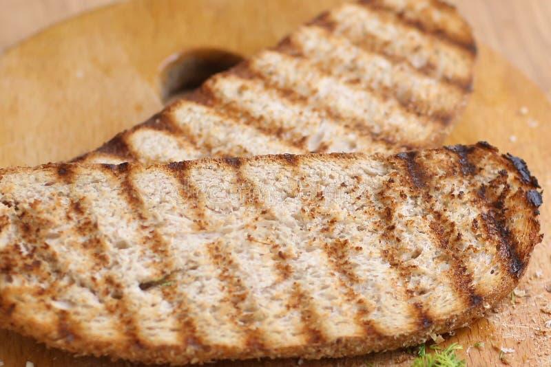 2 зажаренных куска тоста хлеба с shreded укропом на конце доски кухни вверх по фото стоковое фото rf