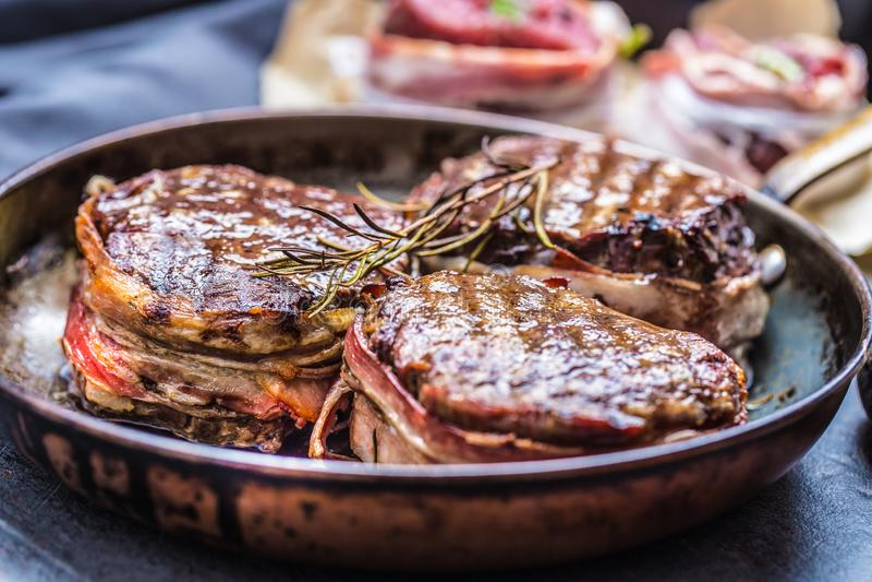 3 зажарили бекон tenderloin говядины покрытый стейками на жаря PA стоковая фотография
