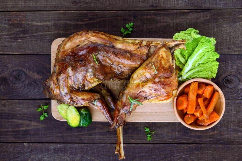 Зажарьте в духовке всего кролика на деревянной доске с испеченными морковами и ростками Брюсселя на темной предпосылке празднична стоковые фотографии rf