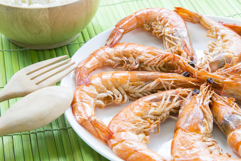 Зажарьте в духовке морепродукты креветок на белом блюде и деревянный kitchenware с стоковые фото