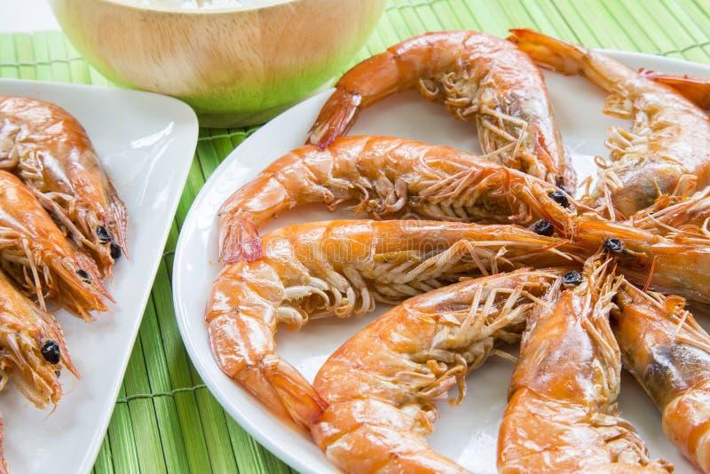 Зажарьте в духовке морепродукты креветок на белом блюде и деревянный kitchenware с стоковая фотография rf