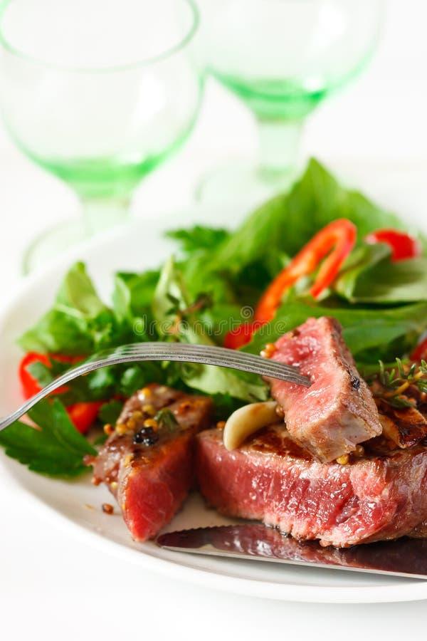 Зажженные стейк и салат говядины. стоковое изображение