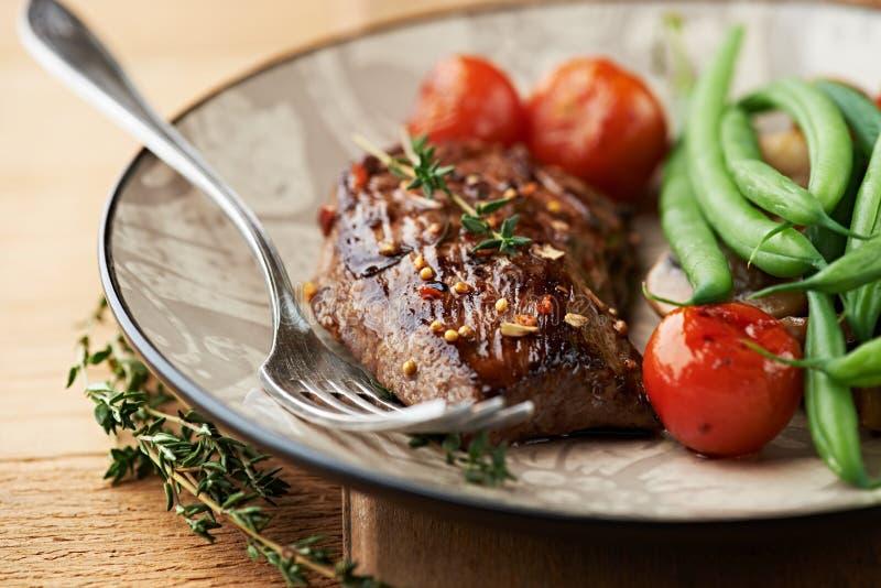 Зажженный стейк говядины с тимианом и овощами стоковое фото