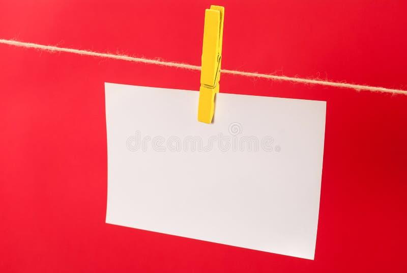 Зажимка для белья и пустая бумага примечания висят на строке на красной предпосылке стоковое изображение rf