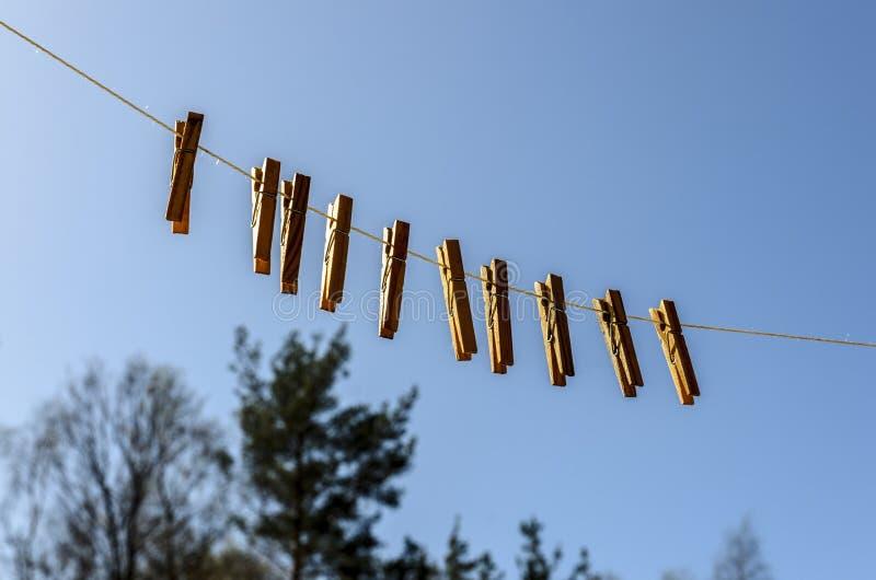 Зажимки для белья для одежд и одежд висят против голубого неба на солнечный день на a стоковое фото