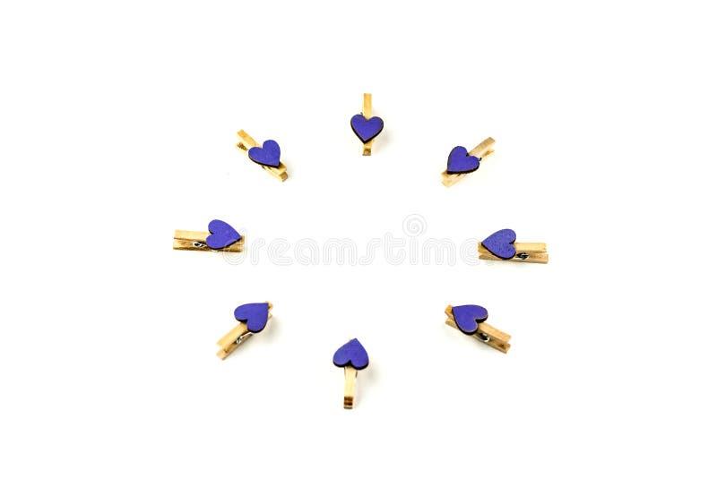 Зажимки для белья с пурпурными сердцами изолированными на белой предпосылке предпосылки Праздничная концепция в минимальном стиле стоковые фото