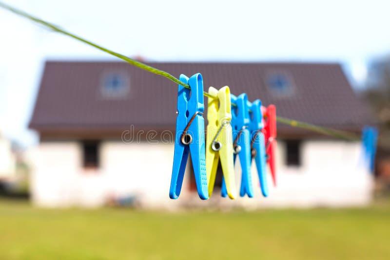 Зажимки для белья вися на шнуре перед домом стоковые изображения