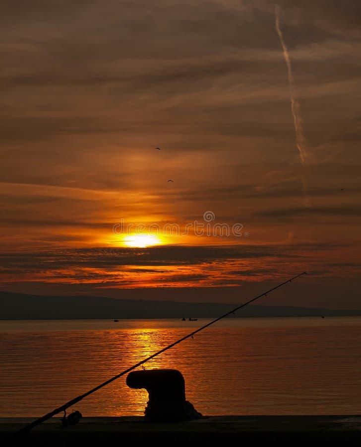 Зажим, и рыболовная удочка на заходе солнца стоковая фотография