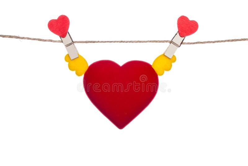 Зажим формы сердца на шпагате, вися подгоняет сердце стоковые изображения