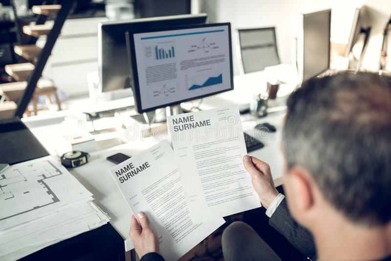 Зажиточный бизнесмен читая CV во время интервью стоковое изображение