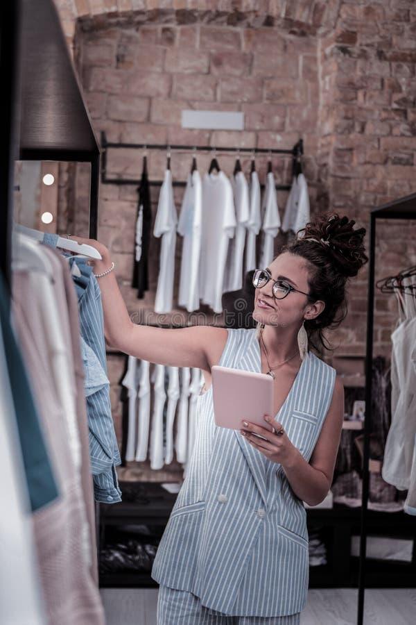 Зажиточный владелец магазина модной одежды проверяя доступный ряд одежд лета стоковые изображения