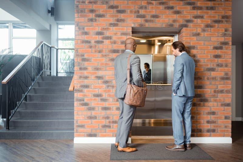 2 зажиточных бизнесмена входя в подъем в деловый центр стоковое фото