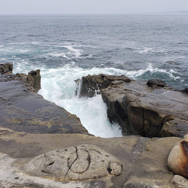 Зазор в стене утеса смотря вне на океане и волнах стоковое фото rf