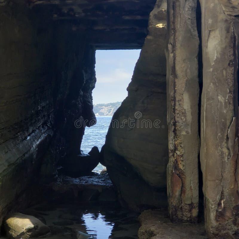 Зазор в стене утеса смотря вне на океане стоковая фотография rf