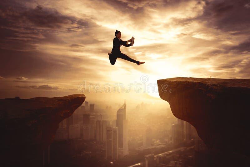 Зазор коммерсантки скача на скале с планшетом стоковое изображение