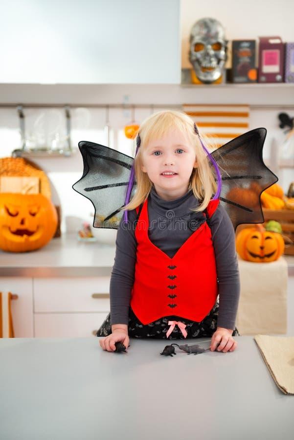 Заинтересованная девушка в костюме летучей мыши хеллоуина в кухне стоковая фотография