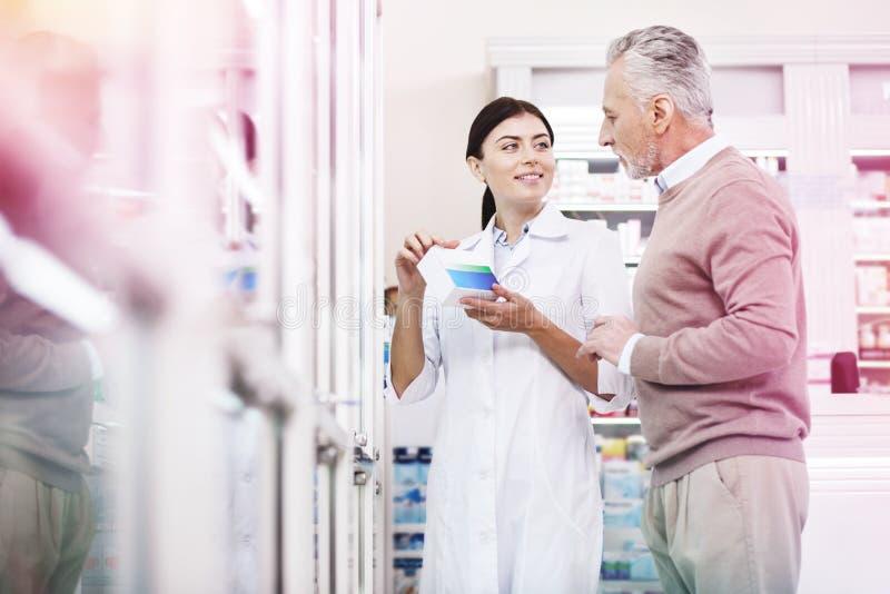Заинтересованный клиент советуя с с druggist о медицинах стоковая фотография
