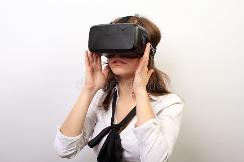 Заинтригованная женщина в белой официально рубашке, нося шлемофон виртуальной реальности 3D трещины VR Oculus, исследуя игру; стоковые изображения rf
