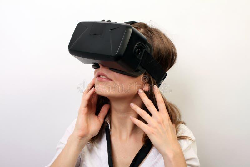 Заинтригованная женщина в белой официально рубашке, нося шлемофон виртуальной реальности 3D трещины VR Oculus, исследуя игру стоковые изображения rf