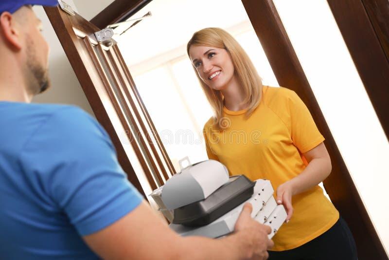 Заказ женщины получая от курьера на двери Доставка еды стоковое изображение rf